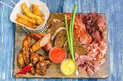 啤酒的快餐-香肠、冷的公猪、鸡腿、调味汁、面包和葱 免版税库存照片