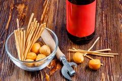 啤酒的构成在一张土气木桌上的在一个碗咸快餐和瓶盖启子旁边 图库摄影