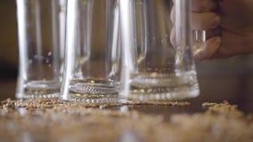 啤酒站立在酒吧特写镜头的桌上的两空的杯 把第三块玻璃放的男性手在桌上 ?? 股票录像