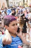 啤酒舍瓦,以色列- 2015年3月5日:一个十几岁的男孩的画象一件蓝色T恤杉的有有一个手机的紫色红色头发的在人群 库存照片