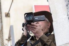 啤酒舍瓦,以色列- 2015年3月5日:一个帽子的一个年长人有一台摄象机的-普珥节 免版税库存照片
