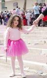 啤酒舍瓦,以色列- 2015年3月5日:一条桃红色女衬衫和裙子的女孩有握她的母亲的手的翼的-普珥节 免版税库存图片