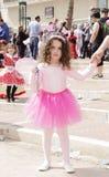 啤酒舍瓦,以色列- 2015年3月5日:一条桃红色女衬衫和裙子的女孩有握她的母亲的手的翼的-普珥节 免版税库存照片