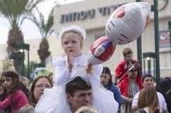 啤酒舍瓦,以色列- 2015年3月5日:一件白色礼服的一个女孩有一个花圈和一个球的在他的父亲的肩膀-普珥节 库存照片