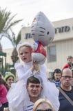 啤酒舍瓦,以色列- 2015年3月5日:一件白色礼服的一个女孩有一个花圈和球全部赌注的在他的父亲的肩膀-普珥节我 免版税库存照片