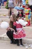 啤酒舍瓦,以色列- 2015年3月5日:有礼服的米老鼠吃在街道上的一个女孩的妈妈棉花糖-普珥节狂欢节  库存图片