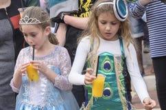 啤酒舍瓦,以色列- 2015年3月5日:狂欢节服装的两个女孩在街道上喝橙汁-普珥节的 库存图片