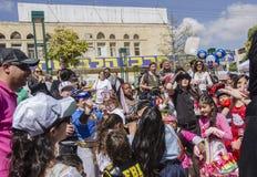 啤酒舍瓦,以色列- 2015年3月5日:狂欢节服装的孩子捉住在普珥节宴餐的礼物  免版税图库摄影