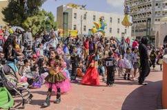 啤酒舍瓦,以色列- 2015年3月5日:狂欢节服装的孩子有他们的在街道上的父母的为庆祝普珥节 免版税库存照片