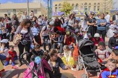 啤酒舍瓦,以色列- 2015年3月5日:狂欢节服装的孩子有他们的在街道上的父母的为庆祝普珥节 库存照片