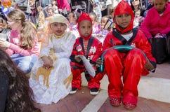 啤酒舍瓦,以色列- 2015年3月5日:猩红色和白色狂欢节服装的孩子-在街道上-普珥节 库存图片