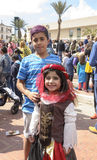 啤酒舍瓦,以色列- 2015年3月5日:男孩和女孩东方服装的在街道上在人群在普珥节节日  库存图片
