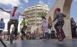 啤酒舍瓦,以色列- 2015年3月5日:男孩和女孩在自行车执行了与在街道场面的一个轮子-普珥节 库存照片