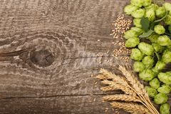 啤酒花球果树框架与麦子的耳朵的在老木背景的 与拷贝空间的顶视图您的文本的 免版税库存照片