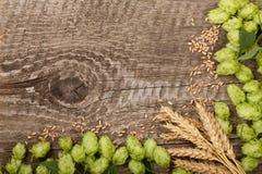 啤酒花球果树框架与麦子的耳朵的在老木背景的 与拷贝空间的顶视图您的文本的 免版税库存图片