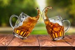 啤酒飞溅在两块玻璃中在反对公园的木桌上 免版税库存照片