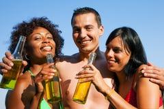 啤酒饮用的朋友组游泳衣 库存图片