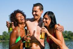 啤酒饮用的朋友编组游泳衣 库存照片