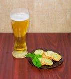 啤酒,与蓬蒿的面包干在木表面上的一个茶碟 库存图片