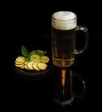啤酒,与蓬蒿的面包干在黑暗的背景的一个茶碟 库存图片
