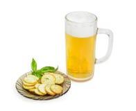 啤酒,与蓬蒿的面包干在轻的背景的一个茶碟 免版税库存照片