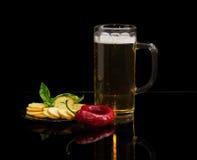 啤酒,面包干,蓬蒿,在一个茶碟的辣椒在黑暗的背景 免版税图库摄影