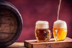 啤酒 两冰镇啤酒 桶装啤酒 草稿强麦酒 金黄的啤酒 金黄强麦酒 两与泡沫的金啤酒在上面 免版税库存照片