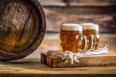 啤酒 两冰镇啤酒 桶装啤酒 草稿强麦酒 金黄的啤酒 金黄强麦酒 两与泡沫的金啤酒在上面 库存图片