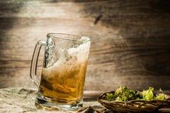 啤酒从在木桌上的杯子溢出 免版税库存图片