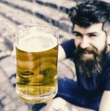啤酒 培养玻璃用桶装啤酒的人 微笑的面孔的行家喝室外的啤酒 欢呼概念 308个黄铜弹药筒报道了遥远的空的地面下跪人步枪射击吊索雪目标冬天 库存图片