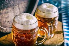 啤酒 OktoberfestTwo冰镇啤酒 桶装啤酒 草稿强麦酒 金黄的啤酒 金黄强麦酒 两与泡沫的金啤酒在上面 草稿冰镇啤酒 库存图片