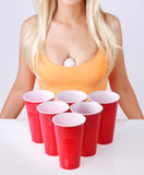 啤酒pong。有乒乓球和白肤金发的女孩的红色塑料杯子性感的无袖衫的 库存图片