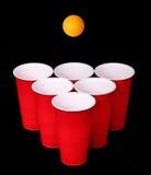 啤酒pong。红色塑料杯子和橙色桌tennise球在黑色 免版税库存图片
