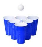 啤酒pong。蓝色塑料杯子和在白色隔绝的乒乓球 免版税图库摄影