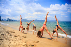 啦啦队员执行手在湿沙子的标度和脚跟舒展 库存照片