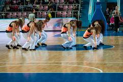 啦啦队欢呼的女孩出现在篮球木条地板 图库摄影