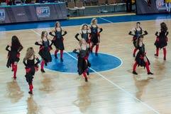 啦啦队欢呼的女孩出现在篮球木条地板 库存照片