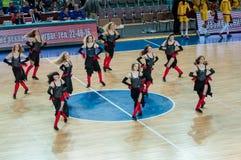 啦啦队欢呼的女孩出现在篮球木条地板 免版税图库摄影