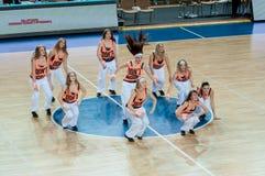 啦啦队欢呼的女孩出现在篮球木条地板 库存图片
