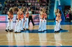 啦啦队欢呼的女孩出现在篮球木条地板 免版税库存照片