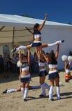 啦啦队欢呼运动员支持组眩晕(头晕)的年轻美丽的女孩欢乐表现  免版税库存照片