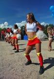 啦啦队欢呼运动员支持组眩晕(头晕)的年轻美丽的女孩欢乐表现  免版税库存图片