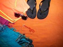 啪嗒啪嗒的响声,毛巾和太阳镜,让` s去海滩 图库摄影