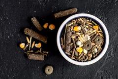 啮齿目动物的干食物在碗黑暗的背景顶视图 库存图片