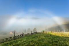 喀尔巴阡山脉的山顶视图 与一条白色彩虹的阴云密布,有蜘蛛网的篱芭 免版税图库摄影