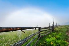 喀尔巴阡山脉的山顶视图 与一条白色彩虹的阴云密布,有蜘蛛网的篱芭 库存照片