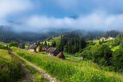 喀尔巴阡山脉的山顶视图 导致村庄,绿草,在云彩的山的路 免版税库存照片