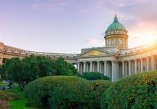 喀山大教堂在圣彼得堡,俄罗斯和喀山摆正与在前景的绿色公园树在日落 免版税库存照片