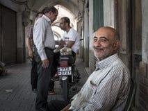 喀山,伊朗- 2016年8月13日:微笑在与伊朗人民的一个闭合值的成交以后的老伊朗蛋卖主在背景中 免版税库存照片