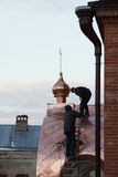 喀山,俄罗斯, 2016年11月19日,修理ortodox老信徒`教会的屋顶两名工作者盖屋顶的人在冬天寒冷天 免版税图库摄影